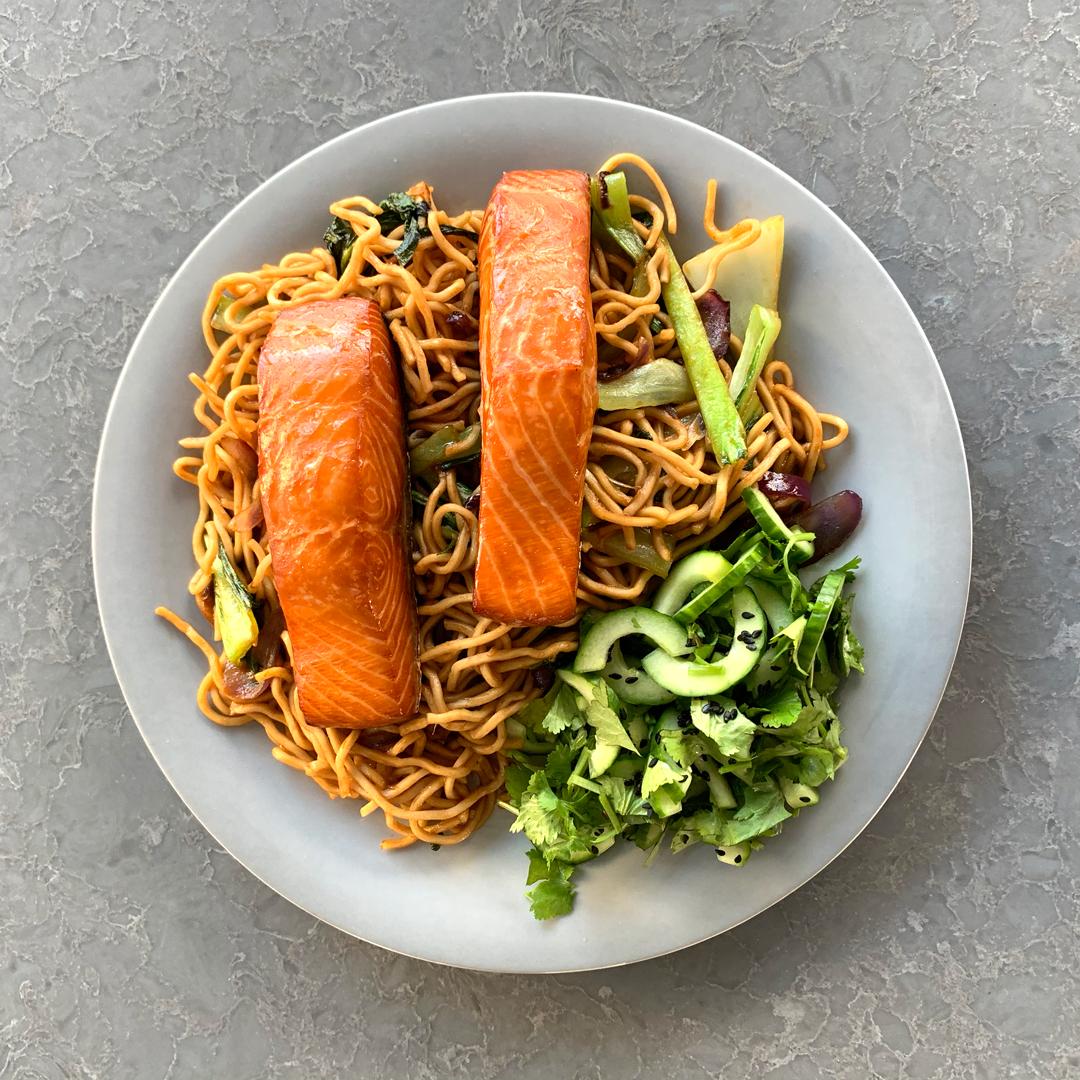 Makaron azjatycki z sosem śliwkowym (hoisin), wędzonym łososiem MOWI i warzywami oraz kwaśno-ostrą sałatką z ogórków z sezamem i kolendrą