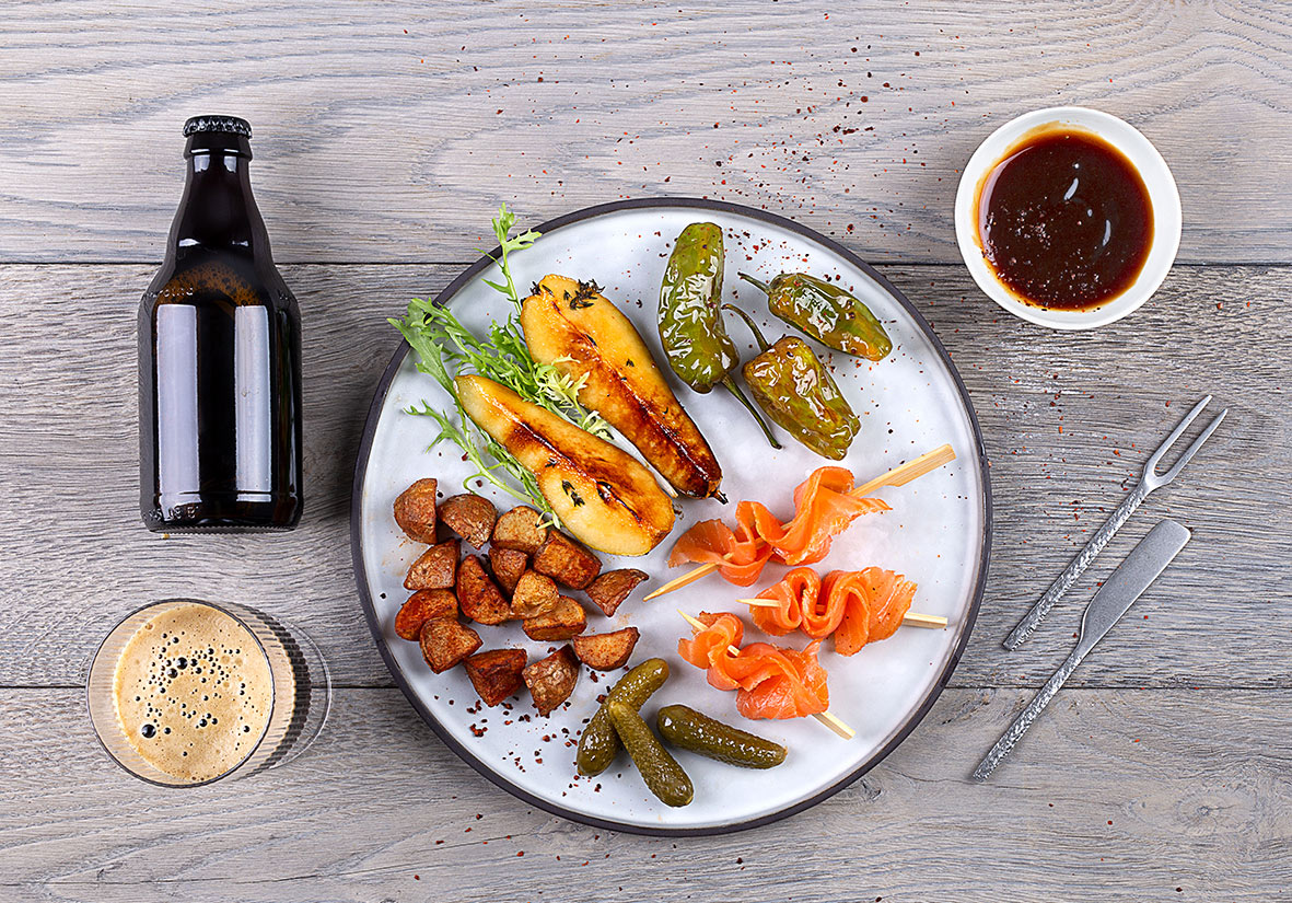Łosoś MOWI wędzony na zimno z sosem z ciemnego piwa, papryczki padron, patatas bravas i gruszka z grilla